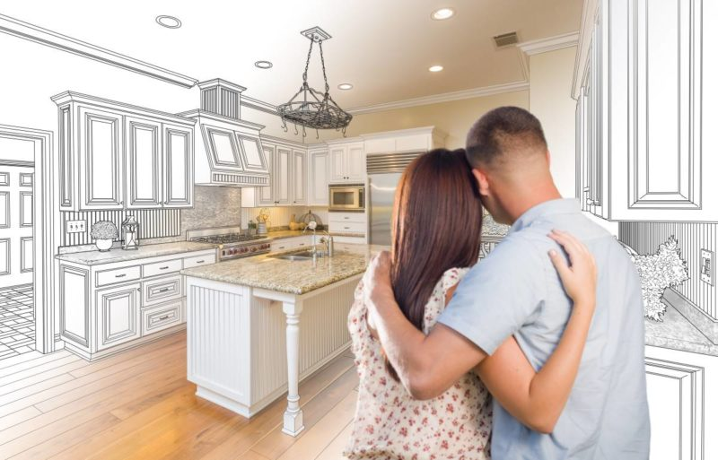 Young couple standing imagining designer's rendering of their renovated kitchen