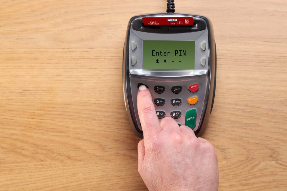 Photo of a woman entering a PIN number with a Debit Card