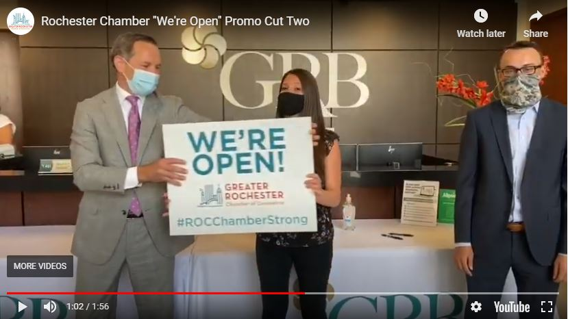 """GRB president and CEO Philip Pecora hands the """"We're Open"""" sign to Commercial Relationship Associate Stephanie DeFazio"""